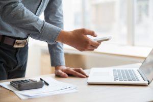 biznesmen-gospodarstwa-smartphone-na-laptopie-w-biurze_1262-2232